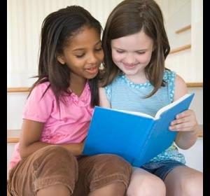 A little white girl reading with a little black girl