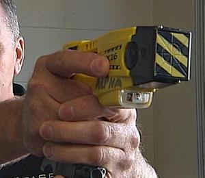 man pointing taser